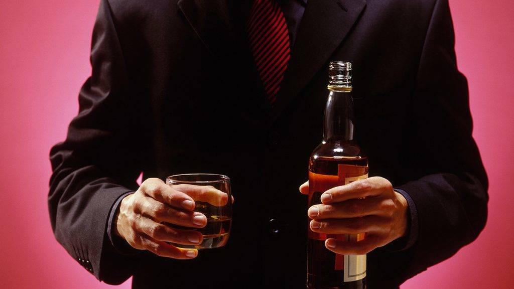 businessman standing with bottle of scotch in his one hand and glass in other