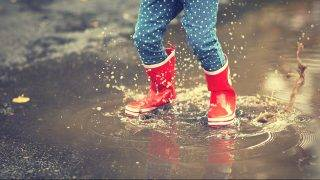 legs of child in red rubber boots jumping in the autumn puddles