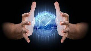 A pair of male hands enveloping a hologram of a monero coin on an isolated dark background