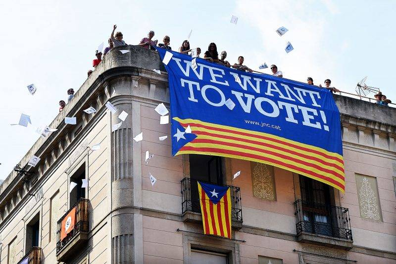 A group of people throw ballots for the October 1 referendum from a building with a banner in favour of the referendum in Sant Jaume square on September 23, 2017 in Barcelona.Spain's Prime Minister Mariano Rajoy asked Catalan separatist leaders today to own up they can't hold an outlawed independence referendum after a crackdown dealt them a serious blow this week. / AFP PHOTO / LLUIS GENE