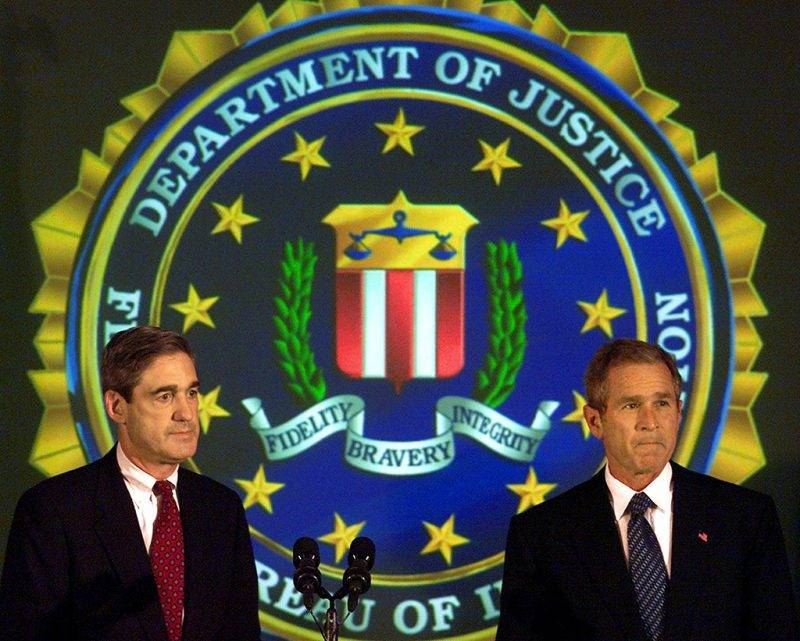 US President George W. Bush (R) and FBI Director Robert Mueller (L) are applauded by a room full of FBI employees after meeting to personally discuss plans to deal with Osama bin Laden and his al-Qaeda terrorist network 25 September 2001 as part of Bush's plan for a war against terrorism in the shadow of the 11 September 2001 terrorist attacks in New York City and at the Pentagon that killed thousands of people.  AFP PHOTO/Paul J. Richards / AFP PHOTO / PAUL J. RICHARDS
