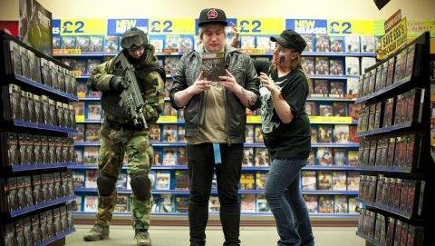 """A handout picture from Blockbuster UK shows a woman dressed as a zombie and a man dressed as a soldier prepare to surprise a customer buying a copy of the Call of Duty: Black Ops 2, the latest title in the recording-breaking videogame franchise, upon it's midnight release in Daventry, Northwest London, late on November 12, 2012. AFP PHOTO/BLOCKBUSTER UK/TOBBY MADDEN   == RESTRICTED TO EDITORIAL USE - MANDATORY CREDIT """"AFP PHOTO / BLOCKBUSTER UK /  TOBY MADDEN"""" - NO MARKETING NO ADVERTISING CAMPAIGNS - DISTRIBUTED AS A SERVICE TO CLIENTS == / AFP PHOTO / BLOCKBUSTER UK / TOBY MADDEN"""