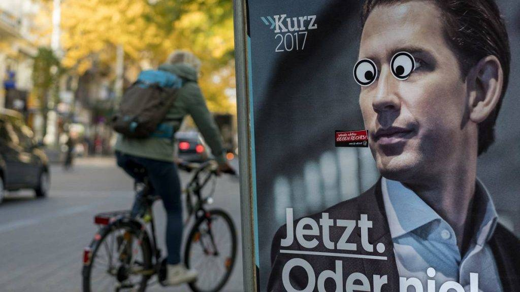 A woman cycles by an election posters of the head of the centre-right People's Party (OeVP) Sebastian Kurz with stickers on his eyes in Vienna, Austria on October 02, 2017.  Kurz is leading opinion polls ahead of snap parliamentary elections on October 15. / AFP PHOTO / JOE KLAMAR