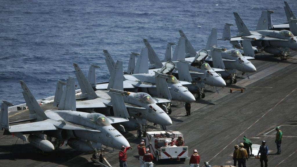 (FILES) This file photo taken on May 24, 2010 shows US Navy crewmen gathering around a line of F-18 jet fighters on the deck of the USS Eisenhower aircraft carrier in the Arabian sea.  Canada now plans to buy a package of used fighter jets instead of new Boeing planes, raising the stakes in a trade spat ahead of talks on October 11, 2017 between Prime Minister Justin Trudeau and President Donald Trump. The Canadian leader's administration is negotiating with Australia to buy used F-18 fighter jets and parts to partially replace its aging fleet.  / AFP PHOTO / MARWAN NAAMANI