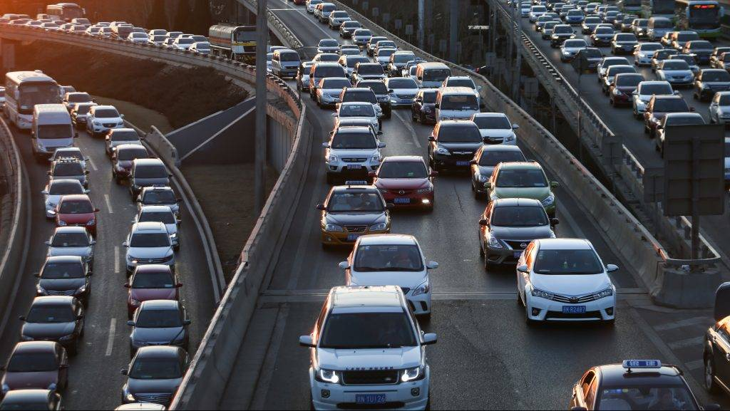 --FILE--Vehicles move slowly in a traffic jam on an elevated highway in Beijing, China, 23 February 2016.  Beijing has preliminarily worked out policies on congestion charge for vehicles, reported National Business Daily on Friday (27 May 2016). Beijing Municipal Environmental Protection Bureau and Beijing Municipal Commission of Transport confirmed that research was conducted to test the policies on Thursday. The policy has been formulated on a base of the similar experience in Singapore, London and Stockholm. The congestion charge policy is to discourage the use of vehicles, especially in rush hour and congested traffic, for the purpose of easing the traffic and the environmental pollution due to excess gas emission. According to data, there are more than 5.6 million cars in Beijing and annual discharge of pollutants is about 700,000 tons, said National Business Daily.