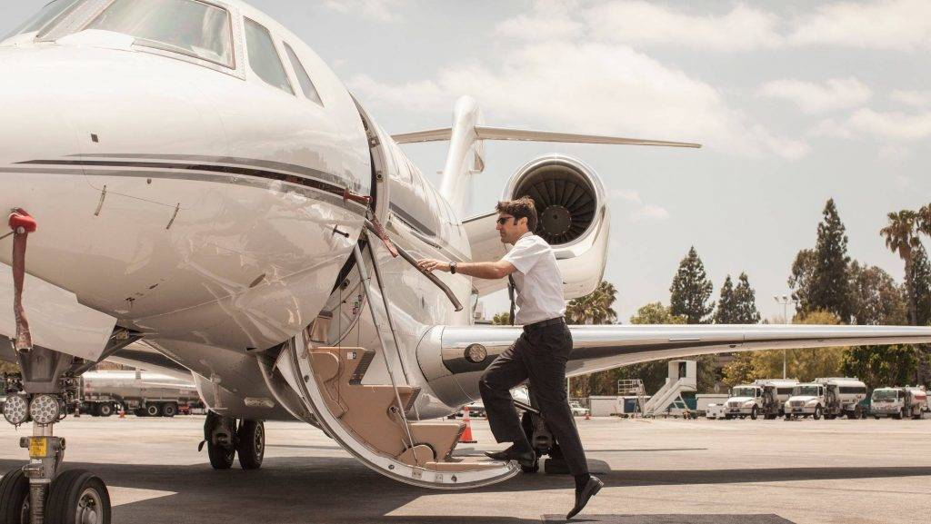 Male private jet pilot boarding plane at airport