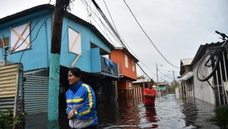 People walk accros a flooded street in Juana Matos, Puerto Rico, on September 21, 2017 as the country faced dangerous flooding and an island-wide power outage following Hurricane Maria. / AFP PHOTO / HECTOR RETAMAL