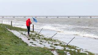A walker fights with his umbrella due to heavy wind as he walks on the seaside on the North Sea Coast in Rastede in Lower Saxony on October 5, 2017 as torrential rain and gusts of winds are expected to hit north and east Germany, rising to hurricane force in cities such as Bremen, Hamburg and Berlin. / AFP PHOTO / dpa / Mohssen Assanimoghaddam / Germany OUT
