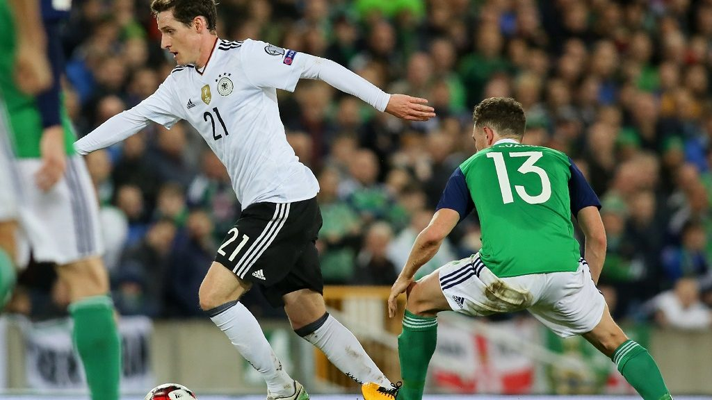 Germany's midfielder Sebastian Rudy (L) runs away from Northern Ireland's midfielder Corry Evans during the FIFA World Cup 2018 qualification football match between Northern Ireland and Germany at the National Football Stadium at Windsor Park in Belfast on October 5, 2017. / AFP PHOTO / Paul FAITH