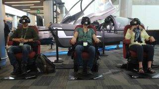Attendees at an Oculus Connect conference in San Jose, California, take a futuristic ride in virtual reality using Samsung Gear VR headsets on October 11, 2017 / AFP PHOTO / Glenn CHAPMAN