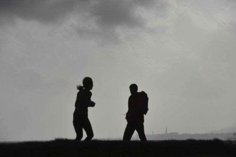"""Pedestrians pass as dark clouds gather at Dublin Bay on October 16, 2017 as Ireland braces for the passing of the storm Ophelia. Schools were closed on October 16 as Ireland braced for an """"unprecedented storm"""", with authorities warning that violent winds, rain and storm surges could pose a risk to life. Ophelia, the largest hurricane ever recorded so far east in the Atlantic Ocean, was downgraded to a storm before it hit the Irish coast but the Met Eireann national weather service warned people to remain indoors.  / AFP PHOTO / Ben STANSALL"""