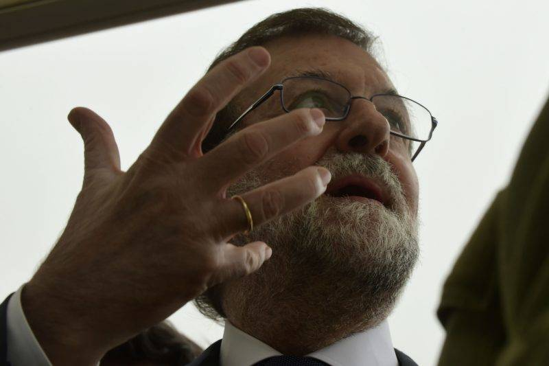 Spanish Prime Minister Mariano Rajoy listens to firemen at a control point in Pazos de Borben, near Redondela, northwestern Spain, on October 16, 2017. At least 27 people have died in fires which have ravaged forests in northern and central Portugal over the past 24 hours, rescuers said, as three people were killed in Spain in blazes sparked by arsonists and fanned by Hurricane Ophelia. / AFP PHOTO / MIGUEL RIOPA