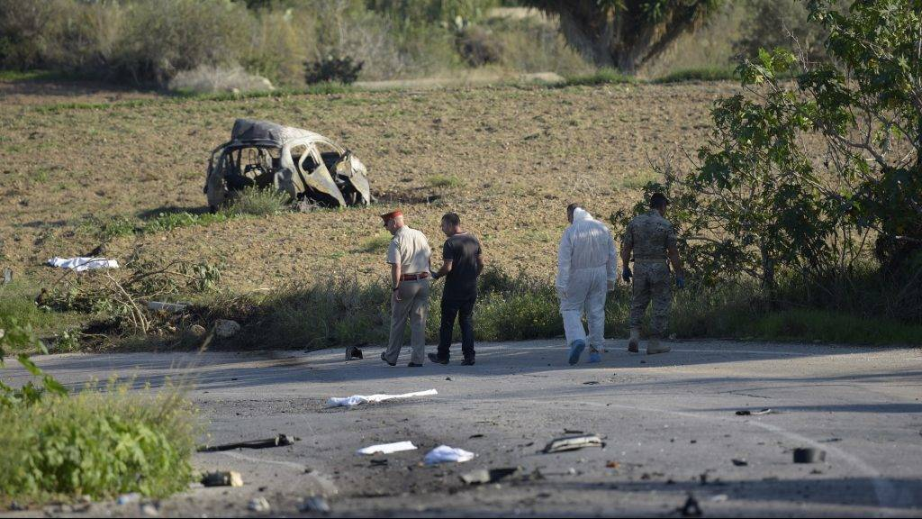 Police and forensic experts inspect the wreckage of a car bomb believed to have killed journalist and blogger Daphne Caruana Galizia close to her home in Bidnija, Malta, on October 16, 2017. The force of the blast broke her car into several pieces and catapulted the journalist's body into a nearby field, witnesses said. She leaves a husband and three sons. Caruana Galizia's death comes four months after Prime Minister Joseph Muscat's Labour Party won a resounding victory in a general election he called early as a result of scandals to which Caruana Galizia's allegations were central.  / AFP PHOTO / STR / Malta OUT