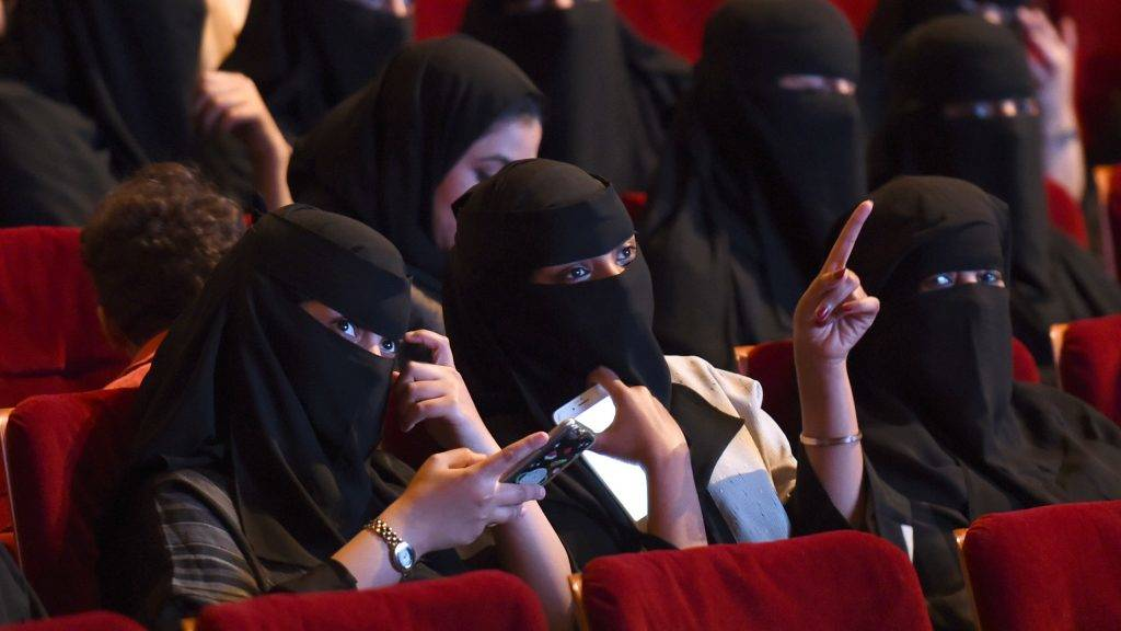 """Saudi women attend the """"Short Film Competition 2"""" festival on October 20, 2017, at King Fahad Culture Center in Riyadh. The rare movie night this week in Riyadh was a precursor to what is expected to be a formal lifting of the kingdom's ban on cinemas, long vilified as vulgar and sinful by religious hardliners. / AFP PHOTO / FAYEZ NURELDINE"""
