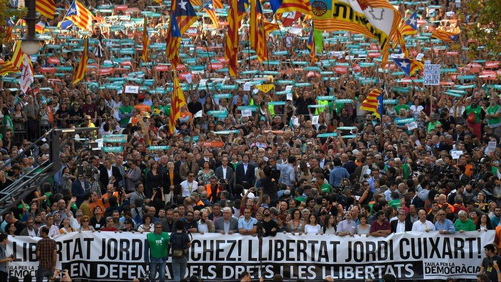 """(C) Catalan government spokesperson Jordi Turull, Catalan regional vice president and chief of economy and finance Oriol Junqueras, Catalan regional president Carles Puigdemont, Catalan parliament president Carme Forcadell and former Catalan regional president Artur Mas stand behind a banner reading """"Free Jordi Sanchez, Free Jordi Cuixart"""" during a demonstration in Barcelona on October 21, 2017 in support of two leaders of Catalan separatist groups, Jordi Sanchez and Jordi Cuixart, who have been detained pending an investigation into sedition charges. Spain announced that it will move to dismiss Catalonia's separatist government and call fresh elections in the semi-autonomous region in a bid to stop its leaders from declaring independence. / AFP PHOTO / LLUIS GENE"""