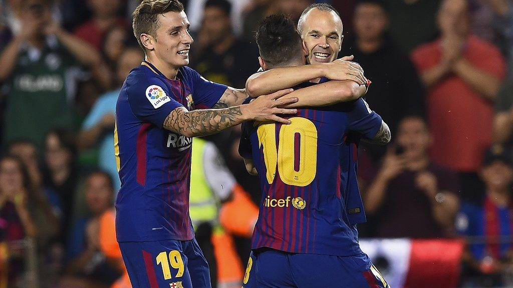 Barcelona's midfielder Andres Iniesta (R) is congratulated by his teammates Barcelona's French defender Lucas Digne (L) and Barcelona's Argentinian forward Lionel Messi after scoring a goal during the Spanish league football match FC Barcelona vs Malaga CF at the Camp Nou stadium in Barcelona on October 21, 2017. / AFP PHOTO / Josep LAGO