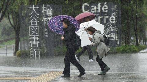 Pedestrians walk along a street under the rain in Tokyo on October 22, 2017.   A powerful typhoon barrelled toward Japan on October 22, with heavy rain triggering landslides and delaying voting at one ballot station as millions struggled to the polls for a national election.  / AFP PHOTO / Kazuhiro NOGI