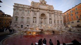 Local police stand by the Trevi fountain in Rome on October 26, 2017 after Italian activist Graziano Cecchini poured red dye into the pool, 10 years after he pulled the same stunt vandalizing one of Rome's most famous monuments.  / AFP PHOTO / FILIPPO MONTEFORTE