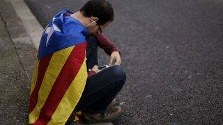 A man wrapped on a Catalan pro-independence 'Estelada' flag listens to the radio with his mobile phone near the Catalan Parliament in Barcelona on October 27, 2017.   The Catalan parliament will vote on how to respond to the central government's planned takeover of Catalan political powers following an outlawed independence referendum.     / AFP PHOTO / PAU BARRENA