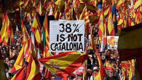 "Protesters wave Spanish and Catalan Senyera flag while holding a sign reading ""38 percent is not Catalonia"" in reference to a referendum voter turnout during a pro-unity demonstration in Barcelona on October 29, 2017. Pro-unity protesters were to gather in Catalonia's capital Barcelona, two days after lawmakers voted to split the wealthy region from Spain, plunging the country into an unprecedented political crisis. / AFP PHOTO / LLUIS GENE"