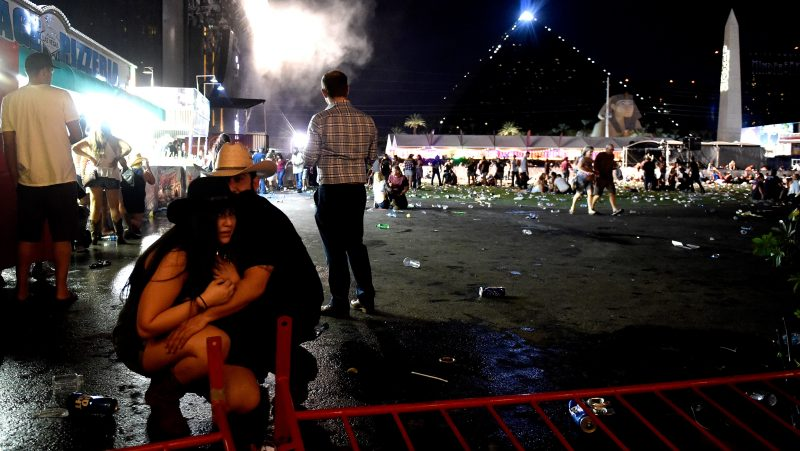 LAS VEGAS, NV - OCTOBER 01: People take cover at the Route 91 Harvest country music festival after apparent gun fire was heard on October 1, 2017 in Las Vegas, Nevada. There are reports of an active shooter around the Mandalay Bay Resort and Casino.   David Becker/Getty Images/AFP