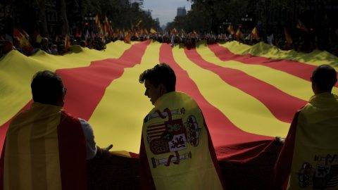 BARCELONA, SPAIN - OCTOBER 12 : People wearing Spanish flags waves a giant Catalonian flag during a demonstration supporting Spain unity on October 12, 2017 in Barcelona, Spain. Spain celebrates its national day as northeastern region of Catalonia faces a crisis due to an independence declaration. Gonzalo Arroyo Moreno / Anadolu Agency
