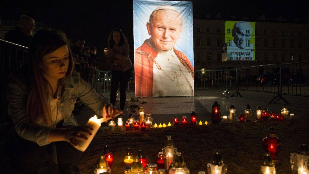A woman lights a candle near John Paul II image during 12th anniversary of death of John Paul II in Warsaw on April 2, 2017.  (Photo by Maciej Luczniewski/NurPhoto)