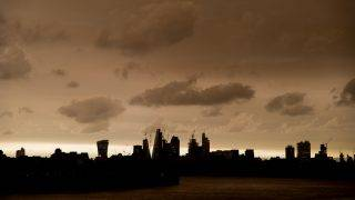 Darkened sky over London is pictured at financial district of Canary Wharf, London on October 16, 2017. The darkening is caused by warm air and dust swept up by storm Ophelia. The sun shone red and the sky darkened to a foreboding orange and brown across parts of Britain.  (Photo by Alberto Pezzali/NurPhoto)