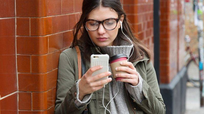 Young woman outside subway station looking at smartphone