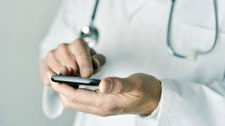 closeup of a young caucasian doctor man wearing a white coat using a smartphone