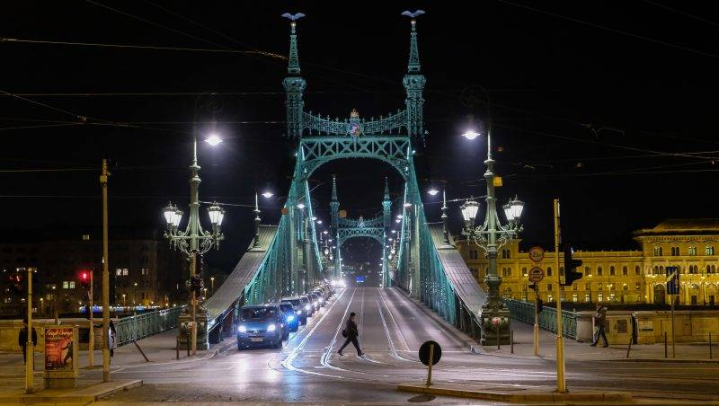 BUDAPEST, HUNGARY - DECEMBER 02:  A person crosses the street in front of one of the bridges over the Danube in the City Centre on December 2, 2016 in Budapest, Hungary. The traditional Christmas market and lights will stay until 1st January 2017.  (Photo by Marco Secchi/Getty Images)