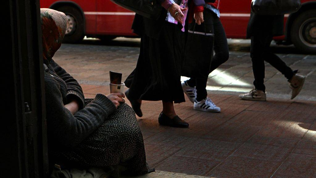 """BOLOGNA, ITALY - MARCH 29: A woman begs for charity from passing women outside the Cattedrale Metropolitana di San Pietro, the city's cathedral dedicated to St. Peter, on March 29, 2017 in Bologna, Italy. Bologna has three nicknames: Situated in the fertile Po River Valley, it is renowned for its cuisine and is known as """"La Grassa"""" (The Fat), home to the oldest university in the Western world it is known as """"La Dotto"""" (The Learned), and because of the terracotta color of its brick buildings along with its  left-leaning communist council it is also know as """"La Rossa"""" (The Red). (Photo by David Silverman/Getty Images)"""