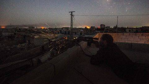 RAQQA, SYRIA - AUGUST 18:  British volunteer fighter 'Macer Gifford' shoots his sniper rifle at ISIS positions in the late hours of the evening on August 18, 2017 in Raqqa Five years ago 'Macer Gifford' (as he likes to be known) was working in London for The Foreign Exchange. He is a 30-year-old, self-confessed 'country-bumpkin' from Cambridgeshire, England. When he saw the atrocities that were happening throughout Iraq and Syria under the banner of the so called Islamic State (ISIL) Macer thought enough was enough. In 2013 he attended a one-week military training course with the Kurdish militia in the mountains of Kurdistan and is now fighting as a sniper with the Syriac Military Council (MFS) on the front line in Raqqa.The MFS is a group of Assyrian Christians who fight alongside the Syrian Democratic Forces (SDF).  The SDF was created in 2015 with the specific purpose of fighting ISIL and was armed by former US President Obama. The second Battle of Raqqa was launched in June 2017 and is the fifth and final phase of the Raqqa Campaign by the SDF.  (Photo by Rick Findler/Getty Images)