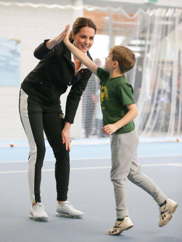 LONDON, UNITED KINGDOM - OCTOBER 31: Catherine, Duchess of Cambridge, high-fives a boy as she takes part in a Tennis for Kids session during a visit at the Lawn Tennis Association (LTA) at the National Tennis Centre on October 31, 2017 in southwest London, England.  The Duchess of Cambridge, who became Patron of the LTA in December 2016, visited the LTA, the national governing body of tennis in Great Britain, where she was briefed on the organisations latest activities and objectives, and had the opportunity to watch a number of tennis demonstrations at the National Tennis Centre's on-court facilities.  (Photo by Daniel Leal-Olivas/WPA Pool/Getty Images)