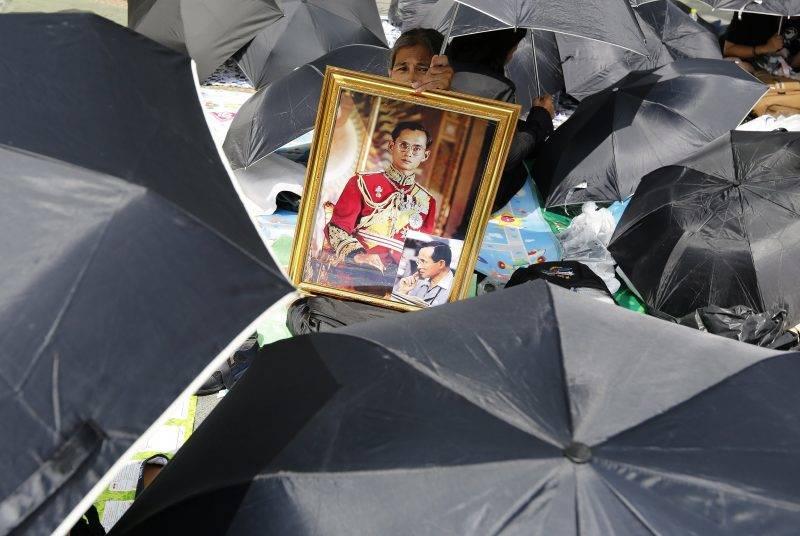 Bangkok, 2017. október 25. Az egyik gyászoló kezében Bhumibol Aduljadedzs, vagyis IX. Ráma thaiföldi király bekeretezett fényképével a néhai uralkodó végsõ búcsúztatásának kezdete elõtt a királyi krematóriumnál Bangkokban 2017. október 25-én. A 2016. október 13-án, 88 éves korában elhunyt királyt október 26-án hamvasztják el, majd helyezik végsõ nyugalomra a bangkoki Nagy Palota közelében megépített mauzóleumban ötnapos ünnepség keretében. (MTI/EPA/Pongmanat Tasziri)