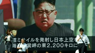Pedestrians walk in front of a large video screen in Tokyo broadcasting a news report showing North Korean leader Kim Jong-Un, following a North Korean missile test that passed over Japan on September 15, 2017. North Korea fired a ballistic missile over Japan and into the Pacific on September 15, responding to new UN sanctions with what appeared to be its furthest-ever missile flight amid high tensions over its weapons programmes. / AFP PHOTO / Toru YAMANAKA