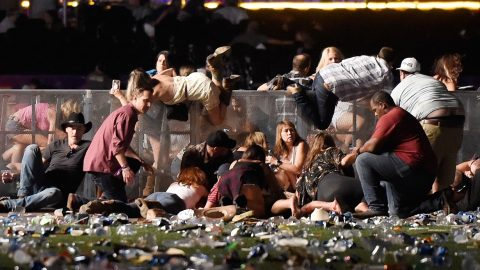 LAS VEGAS, NV - OCTOBER 01: People scramble for shelter at the Route 91 Harvest country music festival after apparent gun fire was heard on October 1, 2017 in Las Vegas, Nevada. A gunman has opened fire on a music festival in Las Vegas, leaving at least 20 people dead and more than 100 injured. Police have confirmed that one suspect has been shot. The investigation is ongoing.   David Becker/Getty Images/AFP