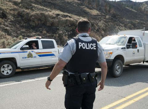 Canadian Mounted Police block traffic from going on highway 97 north of Cache Creek, BC, July 19, 2017 as forest fires rage in western Canada. The provincial government extended a state of emergency and announced aid for tens of thousands of people evacuated because of the disaster. Around 150 fires were burning in British Columbia on the Pacific coast, and more than half of them remained out of control, firefighting officials said. The fires have forced at least 46,000 people from their homes.  / AFP PHOTO / Don MacKinnon
