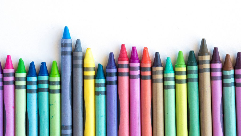 Crayons and pastels lined up isolated on white background for banner