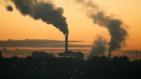 Smoking power plant chimney over a town