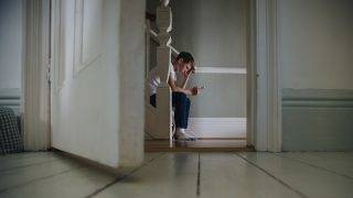 Boy sitting at the bottom of the stairs using a smartphone.