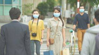 Asian people in the street wearing protective masks
