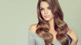 Long haired, appealing model with dense, curled, well cared hair. Portrait of gorgeous young woman with elegant make up and perfect hairstyle. Straight look at camera.