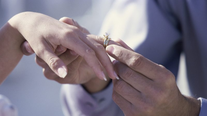 Close-up of a man putting a ring on a woman's finger