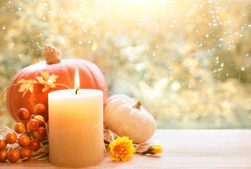 Burning candle, Hokkaido pumpkin and Fall decorations on a windowboard on a rainy day, space for your text