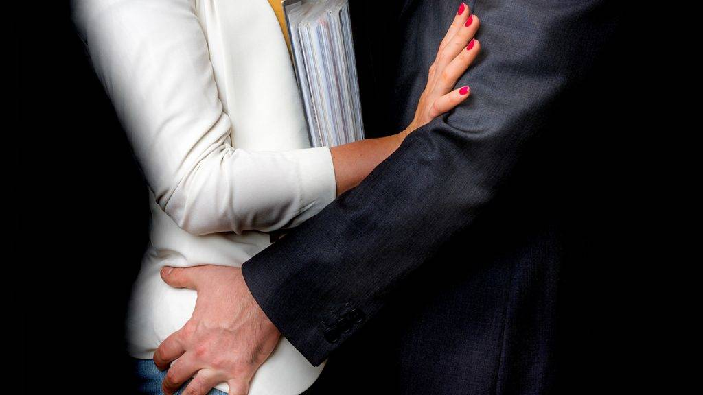 Man touching woman's butt isolated on black - sexual harassment in business office