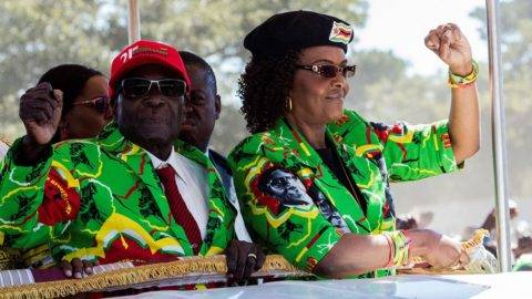 Zimbabwe President Robert Mugabe (L) with his wife Grace Mugabe (R) raise their fists in a vehicle before meeting delegates during a Zimbabwe ruling party Zimbabwe African National Union Đ Patriotic Front (ZANU-PF) youth rally at Rudhaka Stadium in Marondera on June 2, 2017. 