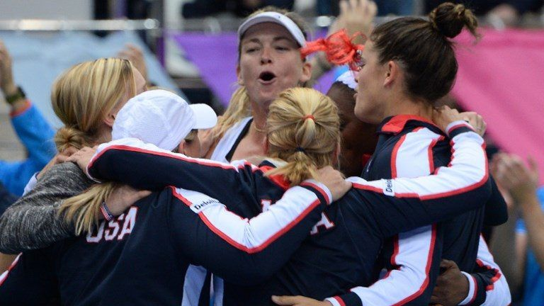 US Coco Vandeweghe (C) and her teammate celebrate their victory over Belarus' in the Fed Cup final tennis match between Belarus and the United States. / AFP PHOTO / MAXIM MALINOVSKY