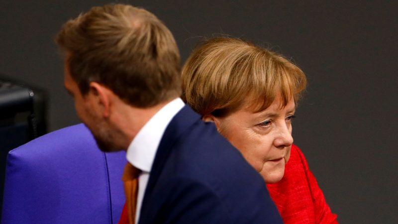 Christian Lindner (L), leader of the free democratic FDP party, walks past German Chancellor Angela Merkel during a session at the Bundestag (lower house of parliament) on November 21, 2017 in Berlin. / AFP PHOTO / Odd ANDERSEN