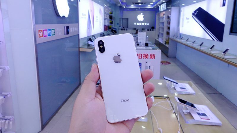 --FILE--A customer tries out an Apple's iPhone X smartphone at a smartphone store in Shenzhen city, south China's Guangzhou province, 30 October 2017.